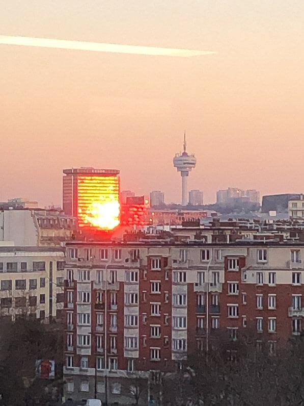 Façade d'immeuble embrasée par le soleil couchant, Paris 19e (75)