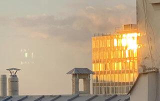 Soleil couchant se reflétant sur la façade d'un immeuble, Paris 19e (75)